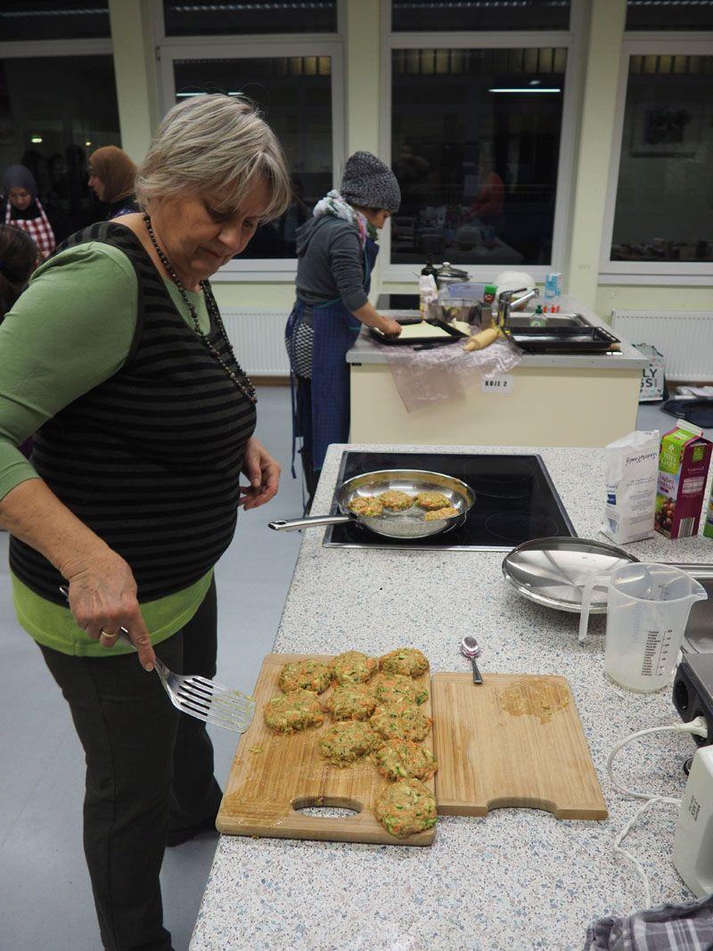 Im Vordergrund wechseln die Zucchini-Puffer vom Brett in die Pfanne. Im Hintergrund guckt der Pizzateig aus dem Backblech.
