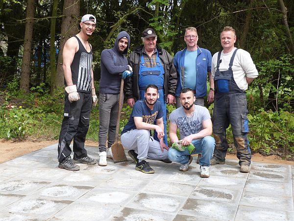 Die glorreichen Sieben posieren stolz auf der fertigen Terrasse